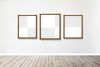 Wooden picture frame mockups hanging on a gray wall